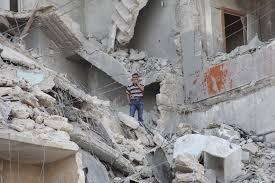 Residente de la ciudad siria de Aleppo en medio de un edificio bombardeado