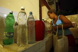 Una residente en el municipio capitalino de Habana del Este organiza en su hogar los envases con agua potable que acaba de acarrear desde la calle